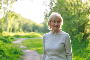 Happy elderly woman in a sunny park
