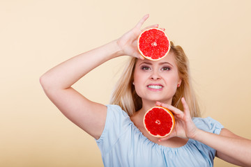 Happy smiling woman holding red grapefruit