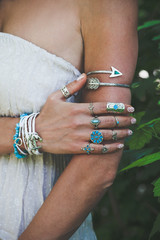 closeup of woman hand and arm with lot of boho style jewrly, rings and bracelets outdoor shot