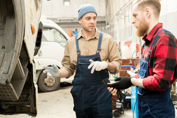 Professional Caucasian auto technicians standing by broken truck in service garage and discussing maintenance