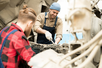 Young professional male mechanic repairing truck in service garage and smiling cheerfully, unrecognizable male colleague helping him