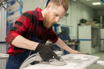 Young professional male mechanic with long beard sanding part of automobile with grinding machine in repair shop