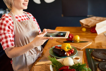 Young woman making photo of fresh vegetables on her touchpad
