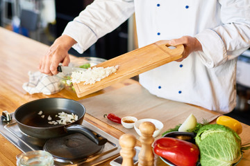 Close-up of chef putting onion in the pan on the stove