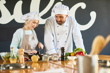 The chef conducts a master class. He is teaching woman to cook different dishes