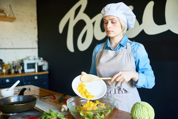 Young female cook preparing salad from vegetables in the kitchen