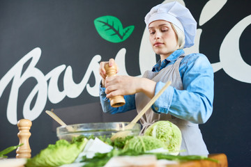 Young woman preparing salad on master class