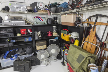 Garage sale set with vintage electronics, music and sports equipment and appliances.