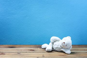 teddy bear on old wood ,blue wall background.