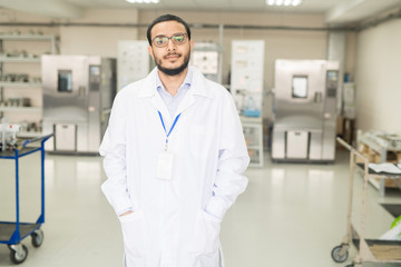 Serious confident handsome young Arabian factory lab technician in lab coat wearing badge and eyeglasses holding hands in pockets and looking at camera in modern innovation plant.
