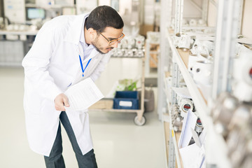 Serious concentrated Arabian engineer in lab coat verifying measuring device list and checking it on shelves in warehouse
