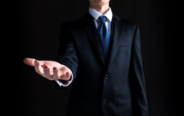 Man in a business suit holding his hand out and showing something