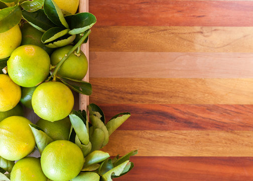 Key lime or Mexican lime in a wooden box on floor, one of main ingredient thai food and traditional pie. horizontal
