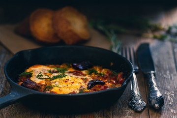 Shakshuka dish in a pan on a wood vintage rustic background
