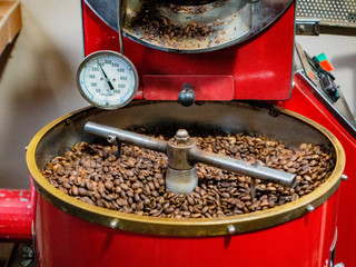 Coffee beans are stirred by machine as they are being cooked in preparation for bagging
