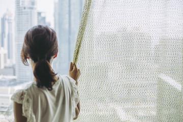カーテン越しに外を眺める女性