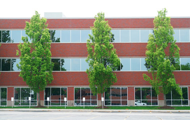 exterior view of office building with green trees in front
