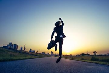 朝日にむかってジャンプするビジネスマン