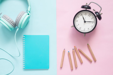 Creative flat lay of headphones, diary, color pencils and alarm clock on pastel color background
