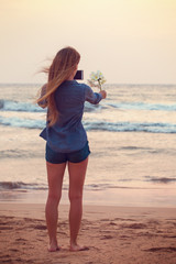 Girl takes pictures of Plumeria flower