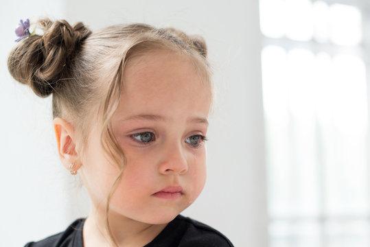 Beautiful sad little girl crying, on background white window
