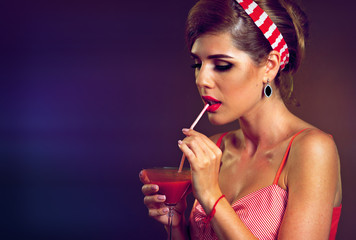 Pin up girl drink bloody Mary cocktail. Pin-up retro female style. Girl wearing red dress seduces men. How to succeed in life. Instructions how to make sexy photo.