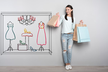 Going shopping. Cheerful emotional student standing with paper bags win her hands and looking satisfied with her new clothes