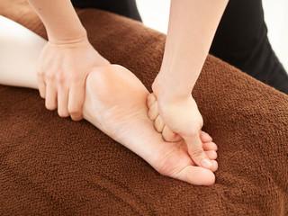 明るい店内で足の裏のリラクゼーションマッサージを受ける女性