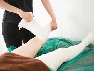 明るい店内で包帯エステの施術を受ける女性