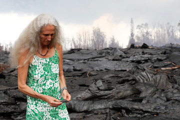 While near the recent Kilauea lava flow, Hannique Ruder marvels at a colorful shard of lava rock she picked up at the flow near Nohea Street in the Leilani Estates near Pahoa, Hawaii
