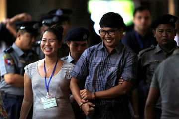 Detained Reuters journalist Wa Lone arrives with his wife Pan Ei Mon escorted by police before a court hearing in Yangon