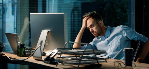 Young tired guy leaning on hand looking in monitor of computer and brainstorming while working late alone.