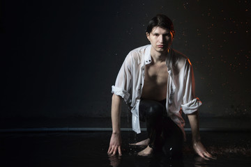 Portrait of attractive young man brunette in wet clothes under droplets of the rain. Studio photo