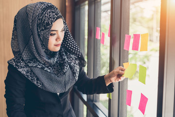 Asian muslim business woman hand picking sticky notes on glass wall.