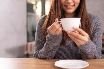An Asian woman with long hair holding a white cup of tea smiling.