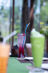 A glass of strawberry soda with white straw put on dining table with green tea in a restaurant background.