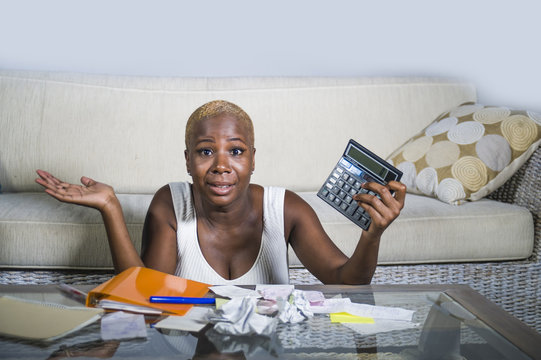 desperate and stressed black afro American woman with calculator and paperwork banking in stress accounting business finance tax and payments