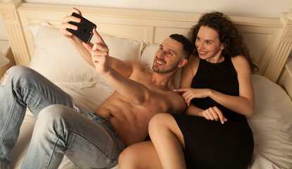 Couple taking selfie. Happy sexy couple taking photo. sexy woman in black dress. Sexy couple in bed. man is embarrassed. Funny faces