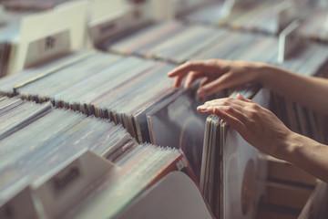 Spoed Foto op Canvas Muziekwinkel Women's hands browsing records close-up