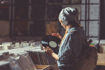 Photo sur Toile Magasin de musique Young girl listening to music on headphones