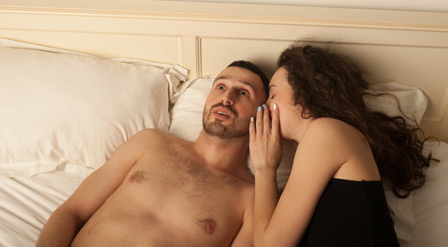 Couple gossiping in a bed. Couple talk in a bed. Couple having arguments