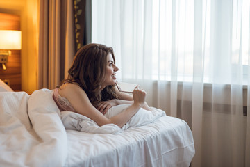 Smiling ttractive girl with phone in bed