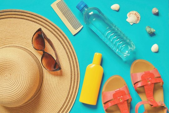 Summer flat lay photo/ Hat, sunglasses, water bottle, comb, sunscreen lotion bottle, seashells and red women's sandals