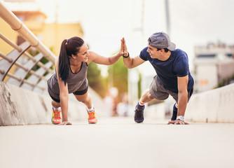 Happy couple doing push-ups outdoors on the bridge