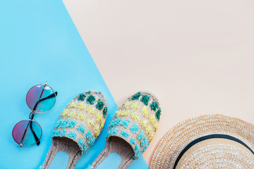 Summer fashion flatlay with gradient round sunglasses, straw hat and espadrille sandals on the two-toned blue and beige background. Perfect beach set for holidays on the sea. Marina style.