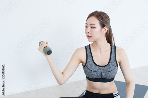 d20aec19d25d6 Young Fitness Asian girl lifting dumbbell