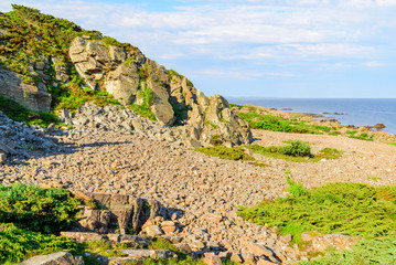 The rocky coastal landscape at Hovs hallar in the Bjare coast nature reserve in Sweden. It is a sunny and calm morning.