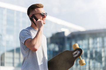 Handsome young man dressed in grey t-shirt and sunglasses holding longboard and talking by smartphone before modern building