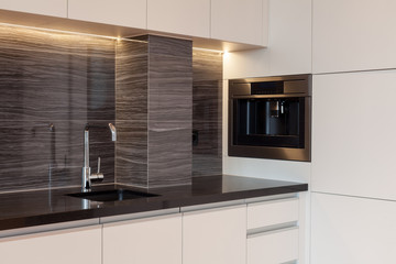 New modern kitchen with built in oven and chrome water tap. LED worktop illumination