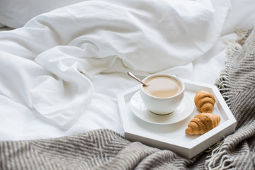 Cozy breakfast in bed, cup of coffee and croissants on white and